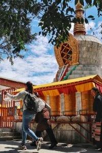 alter Mann läuft mit jungem Mädchen um goldene Gebetsmühlen