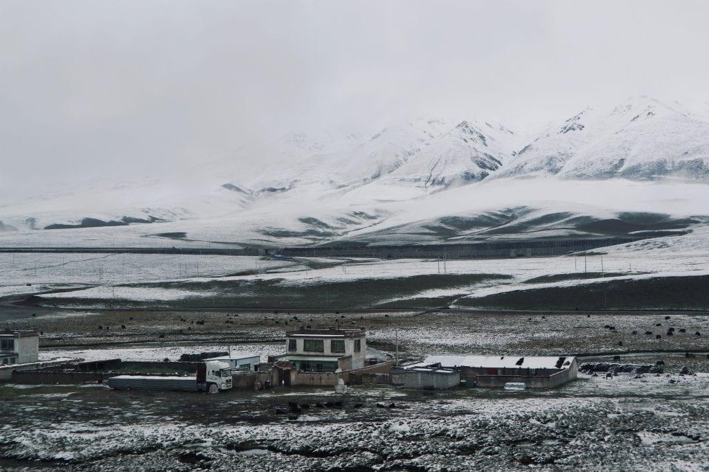Häuser und schneebedeckte Berge in Tibet