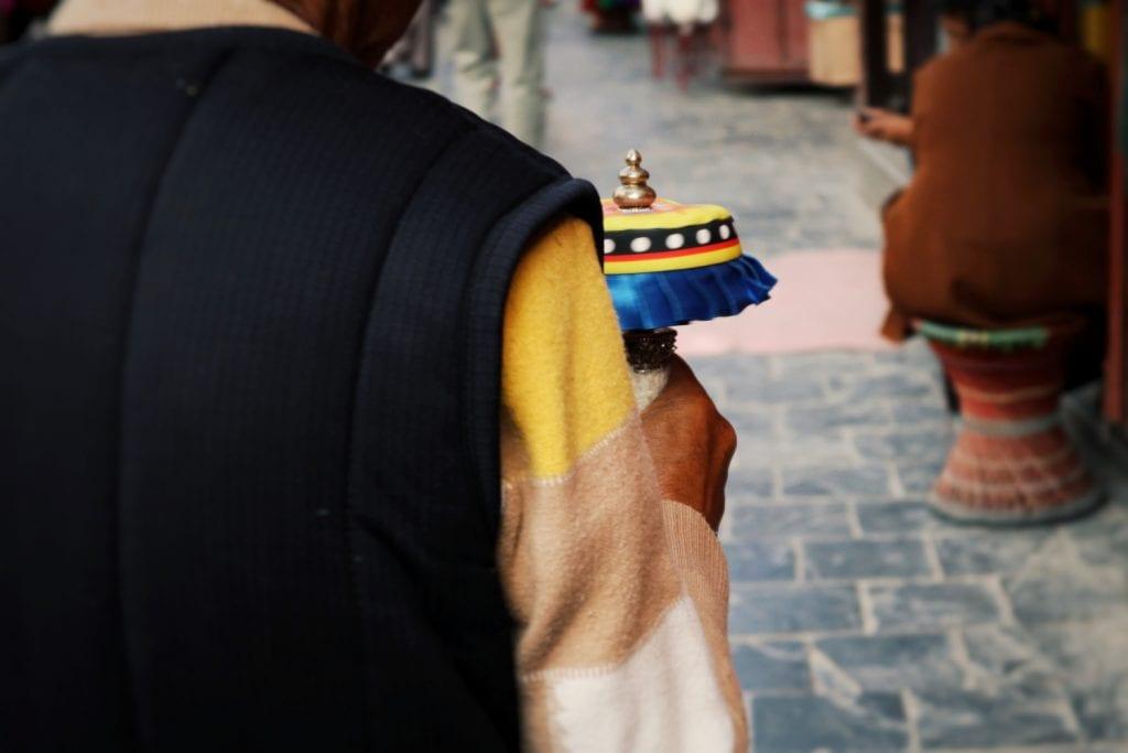 Mann mit Gebetsmühle in Tibet