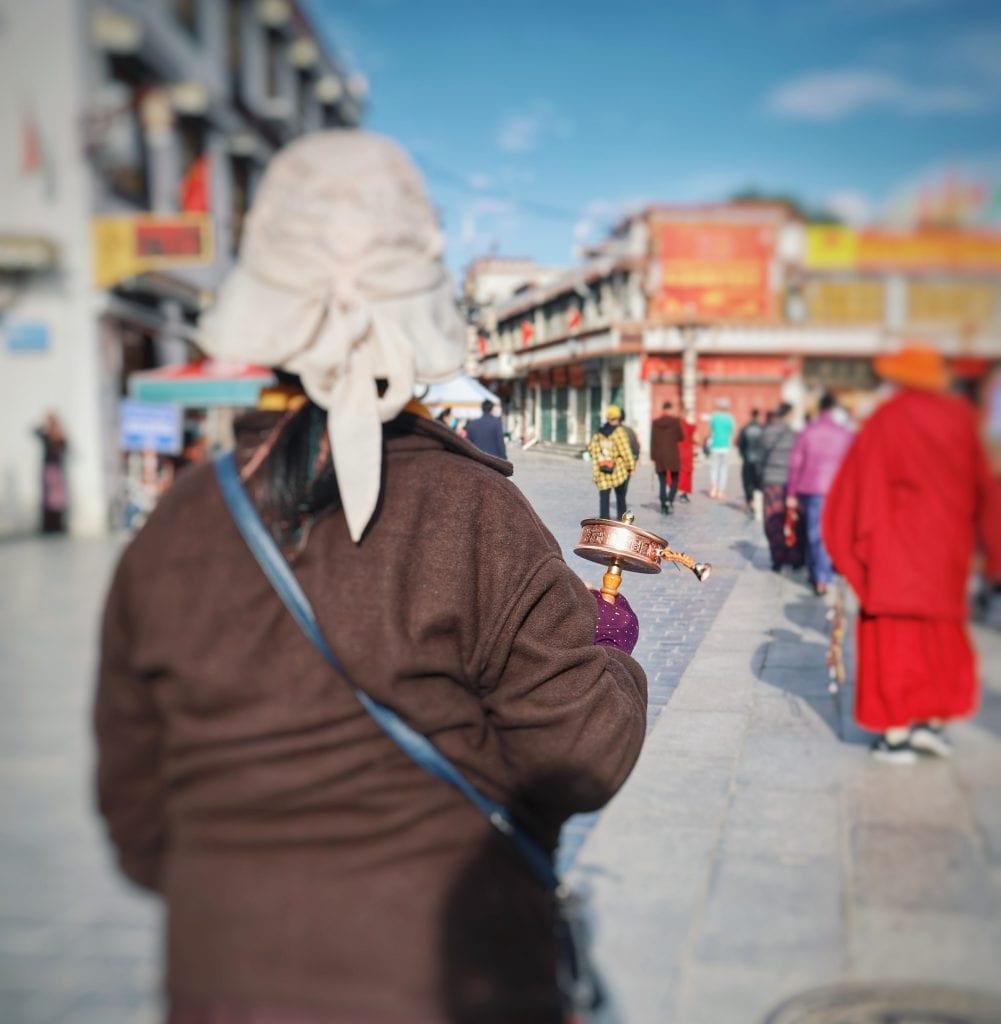 Frau mit Gebetsmühle auf Barkhor Straße