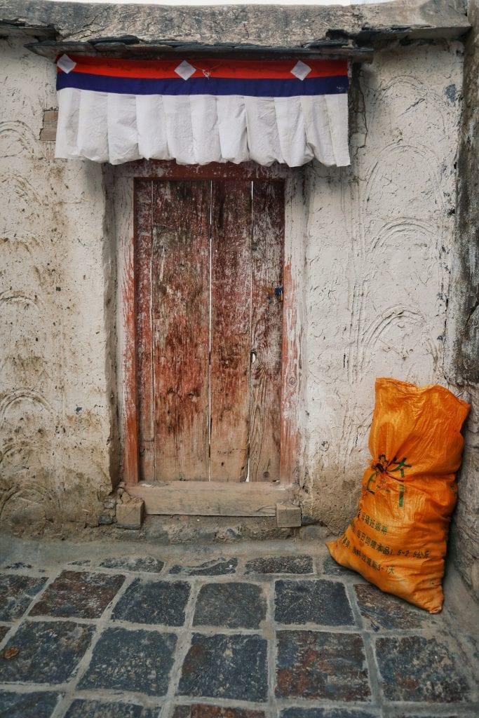 Orangener Sack vor weißem Mönchshaus