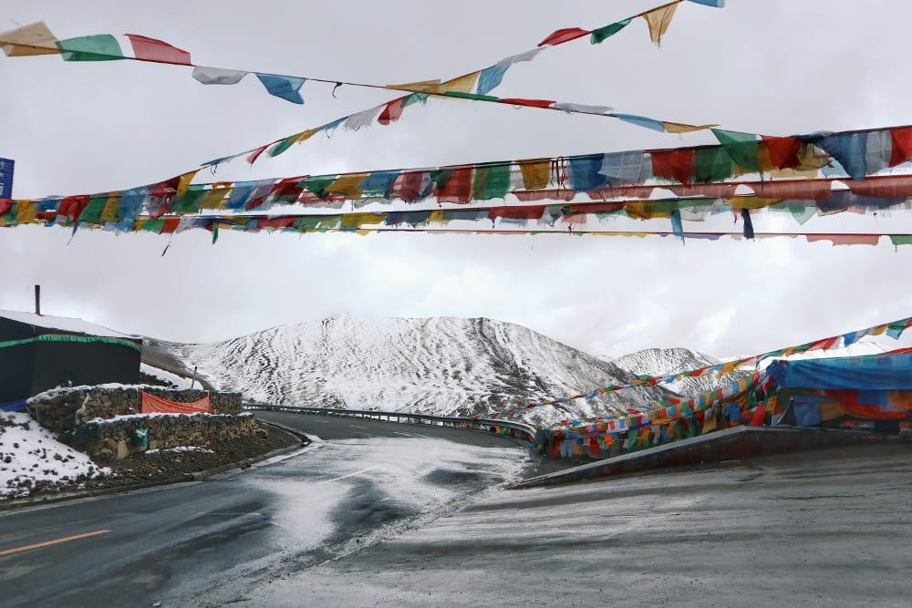 Tibetische Gebetsflaggen mit schneebedecktem Berg