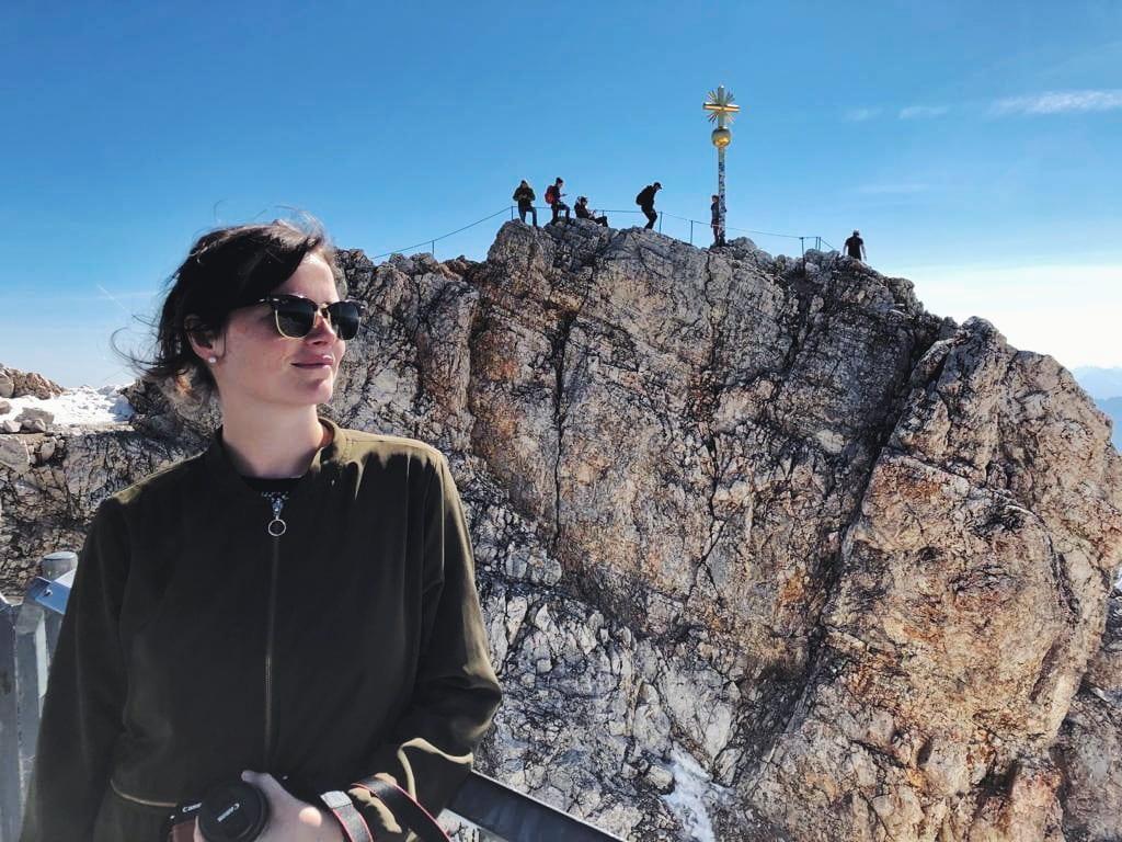 Travellerin Lisa vor dem Gipfelkreuz Zugspitze